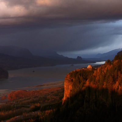 The setting sun lights up Vista House and the Columbia River Gorge, as seen from Chanticleer Point in Oregon.