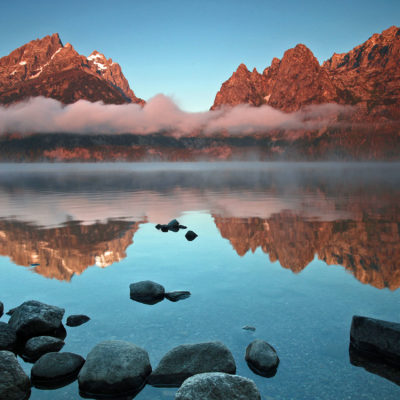 Teewinot and Mount Saint John reflect in Jenny Lake at sunrise at Grand Teton National Park in Wyoming.